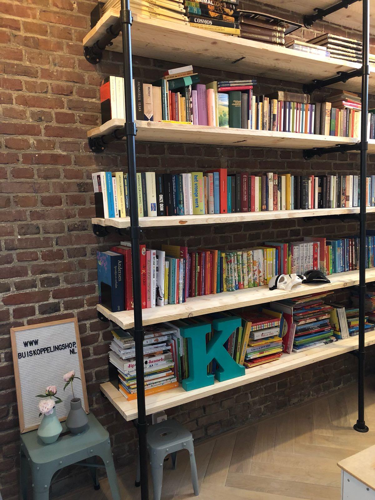 Industriële boekenkast van zwarte steigerbuizen en steigerhout